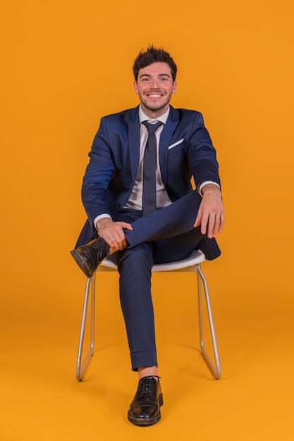 Confiante jovem empresário sentado na cadeira branca contra um fundo laranja Foto gratuita