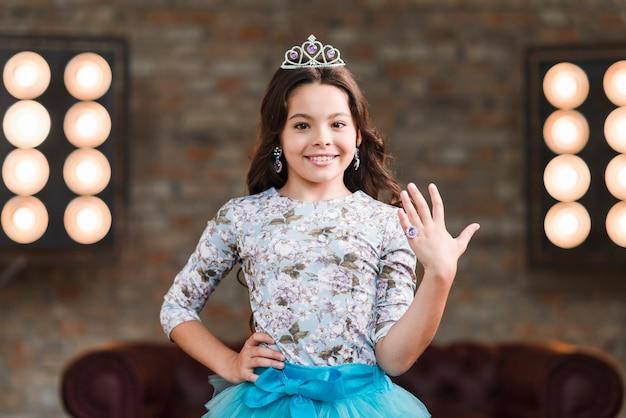 Confiante menina sorridente, mostrando o anel de dedo contra a luz do palco Foto gratuita