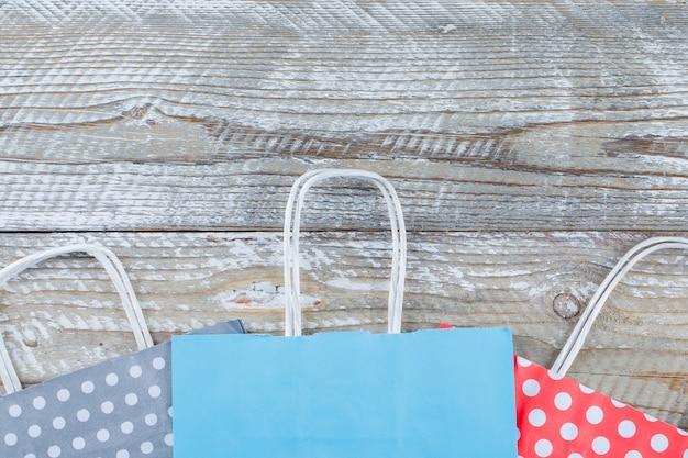 Configuração de aniversário com sacos de presentes de papel no plano de fundo de madeira. Foto gratuita