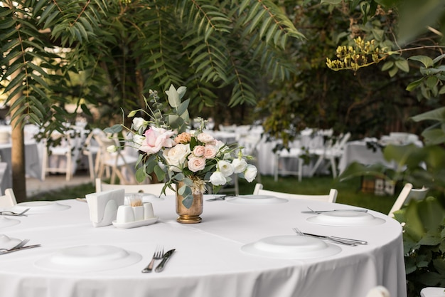 Configuração de mesa de casamento decorada com flores frescas em um vaso de latão. floricultura de casamento. mesa de banquete para os hóspedes ao ar livre com vista para a natureza verde. bouquet com rosas, eustoma e folhas de eucalipto Foto Premium