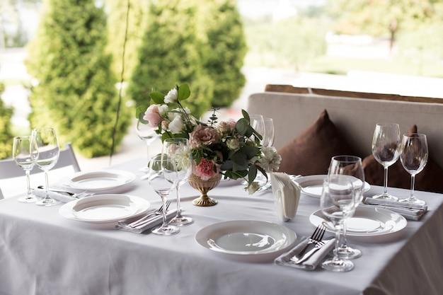 Configuração de mesa de casamento decorada com flores frescas em um vaso de latão. floricultura de casamento. mesa de banquete para os hóspedes ao ar livre com vista para a natureza verde. bouquet com rosas, folhas de eustoma e eucalipto. Foto Premium