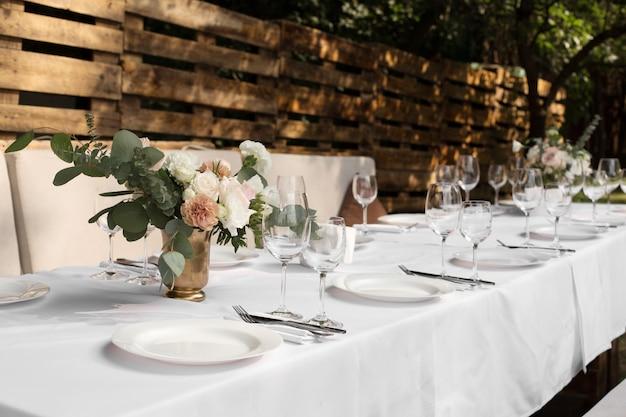 Configuração de mesa de casamento decorada com flores frescas em um vaso de latão. Foto Premium