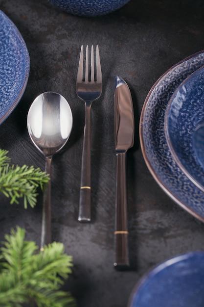 Configuração de mesa de natal. decoração azul escura com galho de árvore do abeto. pratos, taças de vinho e talheres com têxteis decorativos em fundo escuro. Foto Premium