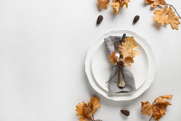 Configuração de mesa de outono elegante com folhas secas e placa branca em branco com espaço de cópia Foto Premium