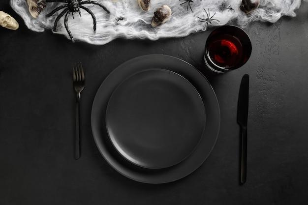 Configuração de mesa preta de halloween com aranha, caveira e teia na mesa preta escura Foto Premium