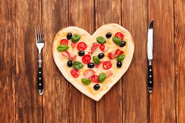 Configuração de mesa romântica com pizza e utensílios de mesa Foto gratuita