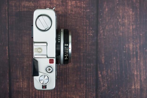 Configuração plana de câmera vintage em um fundo de madeira velho. fundo isolado vista do topo. Foto Premium
