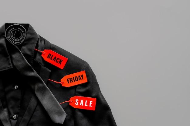 Configuração plana de homens camisa de cor preta, terno, gravata e preços vermelhos em fundo cinza para o conceito de venda de sexta-feira negra. Foto Premium