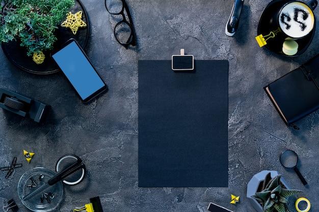 Configuração plana do espaço de trabalho do freelancer. página de papel anexada à área de transferência, tela brilhante do telefone na mesa da mesa. processo de fluxo de trabalho no escritório doméstico. Foto Premium