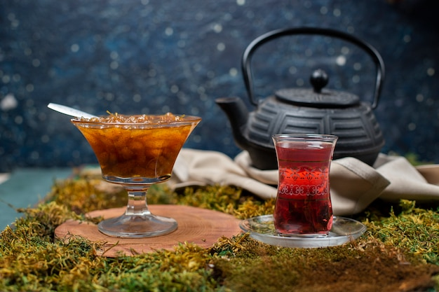 Confiture, copo de chá e chaleira no quadro de grama Foto gratuita