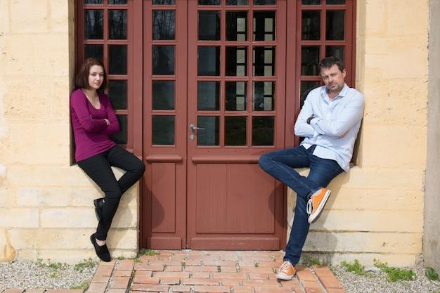 Conflito entre homem e mulher em pé em ambos os lados de uma parede Foto Premium