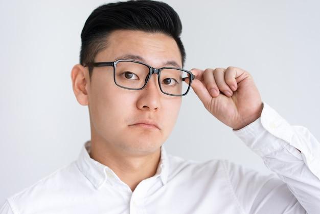 Confuso homem asiático ajustando óculos Foto gratuita