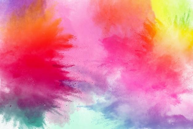 Congelar o movimento de explosões de pó colorido isolado no fundo branco Foto Premium