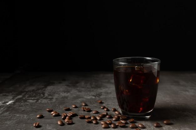 Congele o café preto em um vidro na tabela de madeira. Foto gratuita