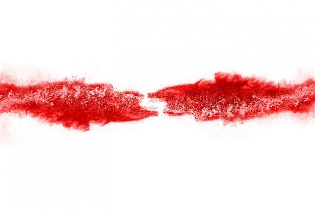 Congele o movimento do pó vermelho explodindo, isolado no fundo branco Foto Premium