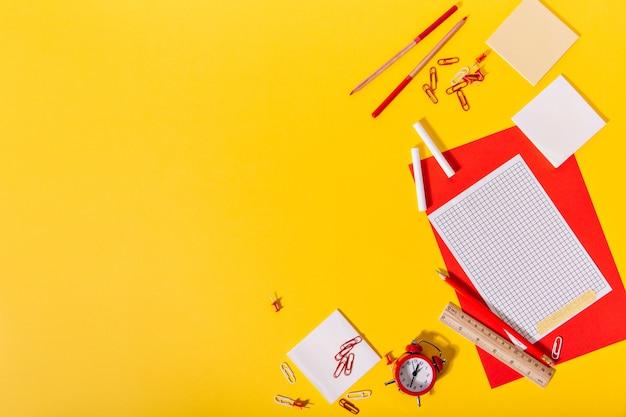 Conjunto brilhante de papelaria escolar composto por vermelho e papel, clipes, giz de cera, lápis e régua de madeira Foto gratuita