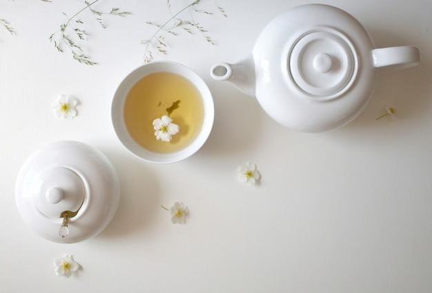 Conjunto com chá verde, xícaras e chaleiras, folhas de hortelã e flores de camomila, com espaço livre para texto, banner longo e largo Foto Premium