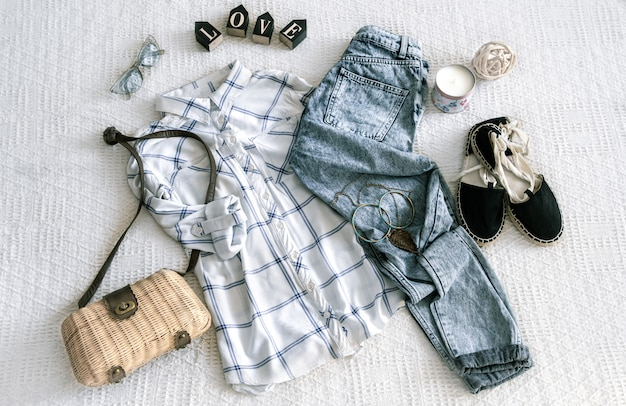 Conjunto com roupas femininas da moda, camisa, jeans e bolsa com acessórios. Foto gratuita