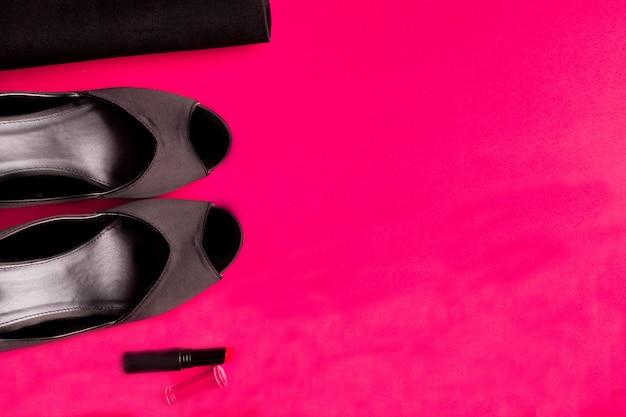 Conjunto de acessórios de moda senhora. preto e rosa. mínimo. sapatos pretos, batom e bolsa rosa. postura plana. Foto Premium