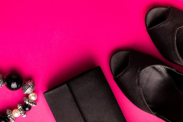 Conjunto de acessórios de moda senhora. preto e rosa. mínimo. sapatos pretos, pulseira e bolsa rosa. postura plana. Foto Premium