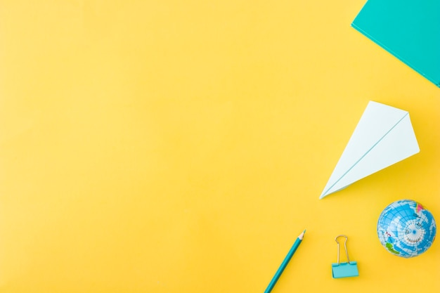Conjunto de acessórios deitado no fundo amarelo Foto gratuita
