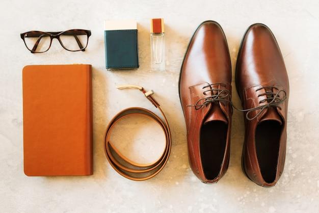 Conjunto de acessórios elegantes para homem em fundo cinza. flat leigos de cinto elegante, óculos, perfume, notebook. conceito de moda de rua para o homem. Foto Premium