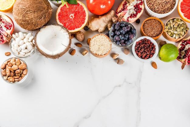 Conjunto de alimentos orgânicos dieta saudável, superalimentos - feijão, legumes, nozes, sementes, verduras, frutas e legumes ... branco. vista do topo Foto Premium