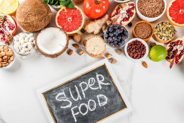 Conjunto de alimentos orgânicos dieta saudável, superalimentos - feijão, legumes, nozes, sementes, verduras, frutas e legumes ... espaço branco cópia de fundo. vista do topo Foto Premium