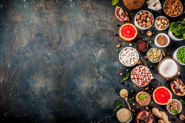 Conjunto de alimentos orgânicos dieta saudável, superalimentos - feijão, legumes, nozes, sementes, verduras, frutas e legumes. fundo azul escuro cópia espaço vista superior Foto Premium