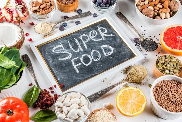 Conjunto de alimentos orgânicos dieta saudável, superalimentos - feijão, leguminosas, nozes, sementes, verduras, frutas e legumes .. espaço branco cópia fundo Foto Premium
