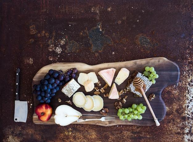 Conjunto de aperitivos de vinho: seleção de queijo francês, favo de mel, uvas, pêssego e nozes na placa de madeira rústica sobre metal escuro grunge. vista do topo Foto Premium