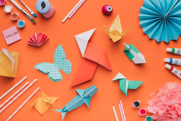 Conjunto de arte de papel origami; pincel; aquarela e palha em pano de fundo laranja Foto gratuita