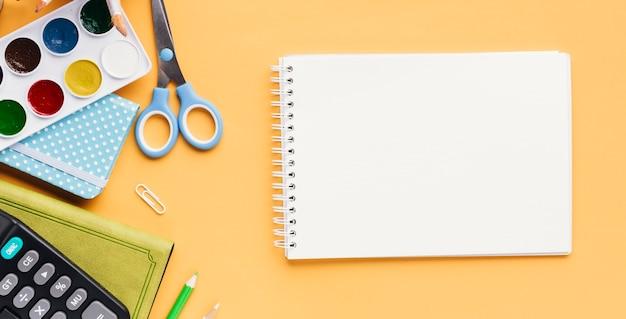 Conjunto de artigos de papelaria ao lado do bloco de desenho Foto gratuita