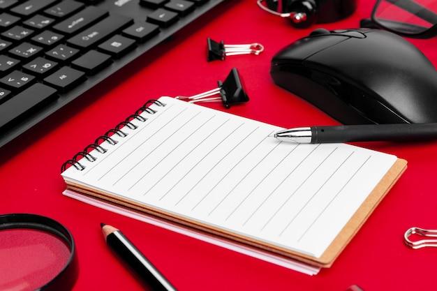 Conjunto de artigos de papelaria na mesa de escritório vermelho Foto Premium