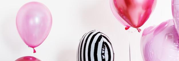 Conjunto de balões em forma de um coração e redondo rosa e listrado na luz de fundo com espaço de cópia. faixa longa e larga. Foto Premium