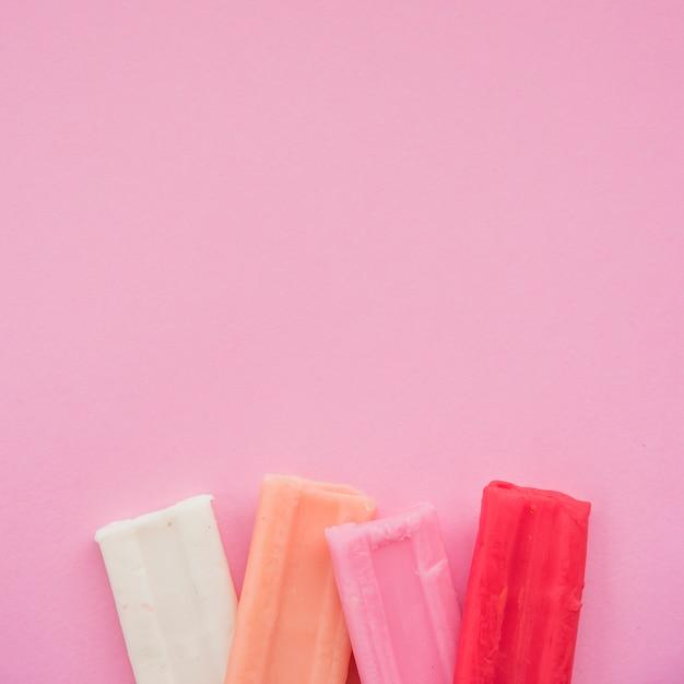 Conjunto de bar de barro colorido no fundo rosa Foto gratuita