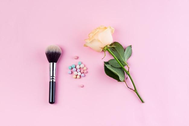 Conjunto de bolas de pó de cosméticos coloridos e escova com rosa sobre fundo rosa. Foto Premium