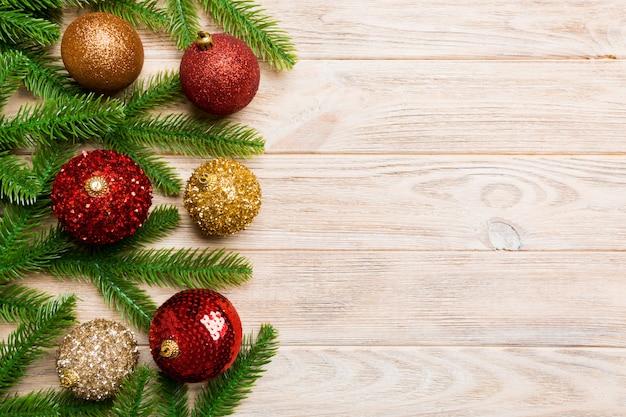 Conjunto de bolas festivas, abeto e decorações de natal em fundo de madeira. vista superior do conceito de ornamento de ano novo com espaço de cópia Foto Premium