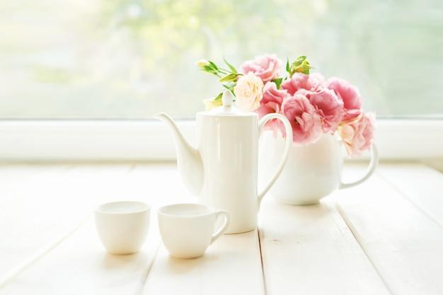 Conjunto de café ao lado de um vaso de flores em uma mesa contra uma janela Foto Premium