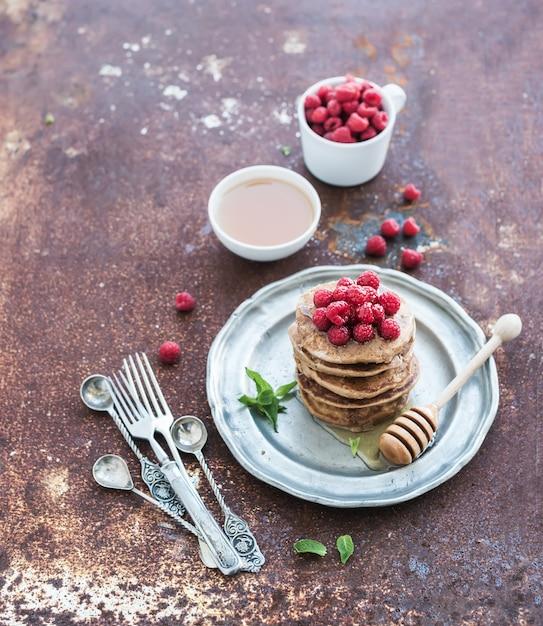 Conjunto de café da manhã. panquecas de trigo sarraceno com framboesas frescas, mel e folhas de hortelã sobre metal grunge Foto Premium