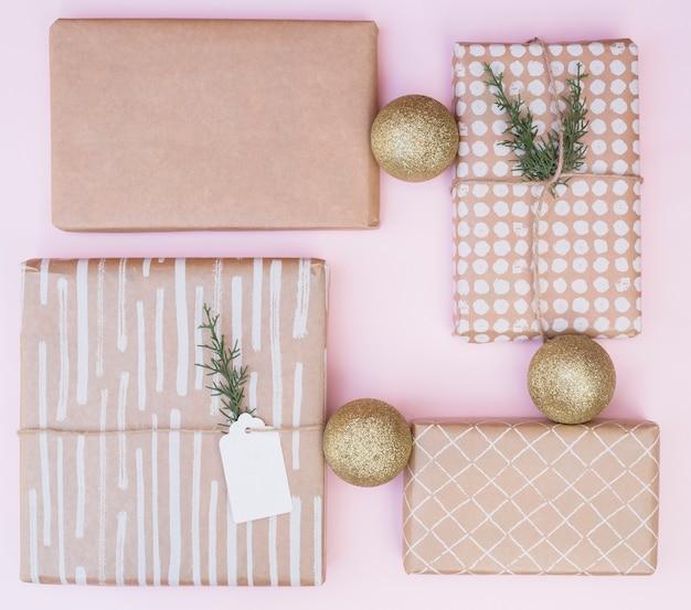 Conjunto de caixas de presentes em envolvimentos perto de bolas de natal Foto gratuita