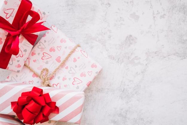 Conjunto de caixas de presentes no envoltório com fita vermelha, arco e torção Foto gratuita