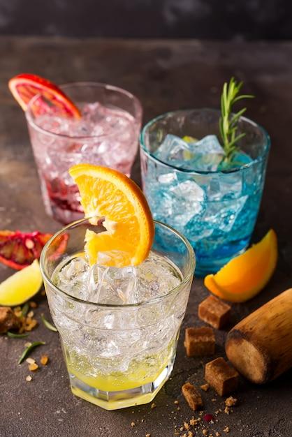 Conjunto de cocktails coloridos com frutas e ervas, açúcar mascavo em fundo de pedra Foto Premium