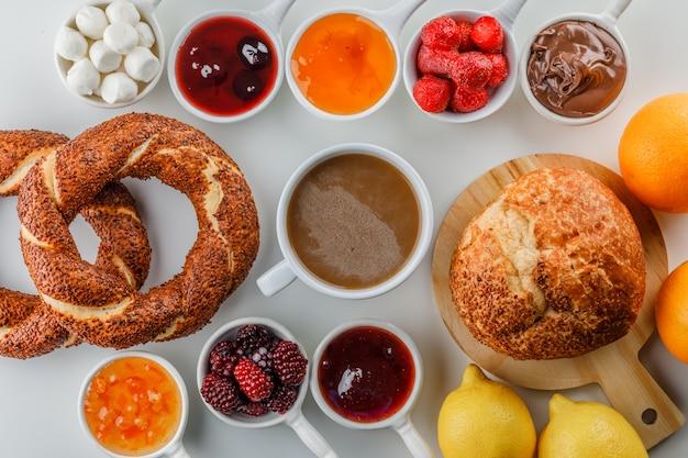 Conjunto de compotas, framboesa, açúcar, chocolate em xícaras, pão turco, pão, laranja e limão e uma xícara de café em uma superfície branca Foto gratuita