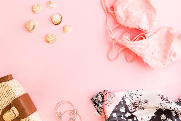Conjunto de conchas e acessórios de férias de praia em fundo rosa Foto gratuita