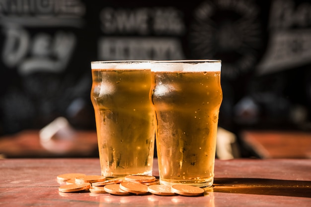 Conjunto de copos de bebida perto de pilha de moedas na mesa Foto gratuita
