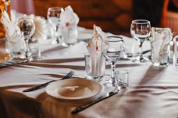 Conjunto de copos e pratos vazios com talheres numa toalha de mesa branca em cima da mesa no restaurante Foto Premium