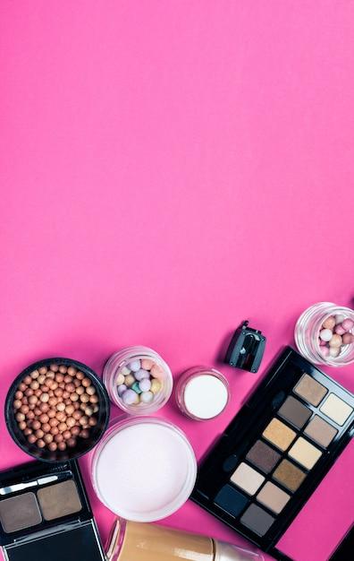 Conjunto de cosméticos coloridos na mesa-de-rosa Foto Premium