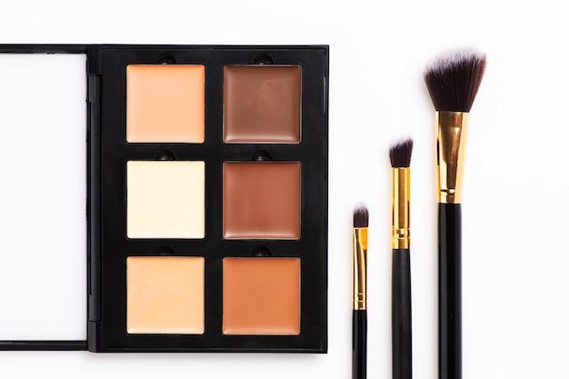 Conjunto de cosméticos decorativos e pincéis na mesa Foto Premium