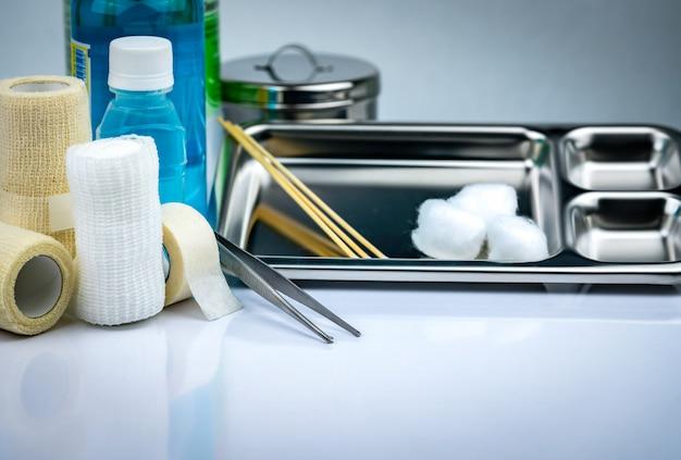 Conjunto de curativos para tratamento de feridas e chapa de aço inoxidável, pinça, copo de iodo, atadura de conformação, atadura de retenção coesa elástica, frasco salino anti-séptico e normal. Foto Premium